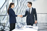 Businesswoman and businessman shaking hands in modern office - BSZF00492