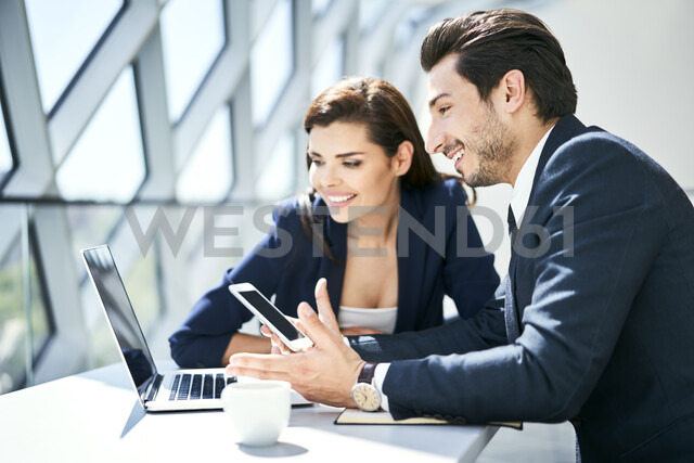 Smiling businesswoman and businessman using laptop and cell phone at desk in modern office - BSZF00495 - Bartek Szewczyk/Westend61