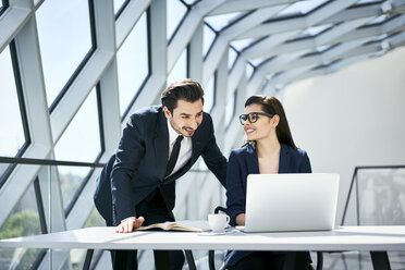 Smiling businesswoman and businessman using laptop at desk in modern office - BSZF00498