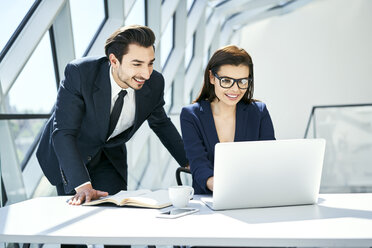 Smiling businesswoman and businessman using laptop at desk in modern office - BSZF00501