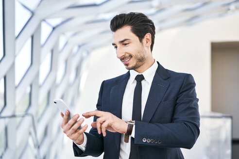 Smiling businessman looking at cell phone - BSZF00504