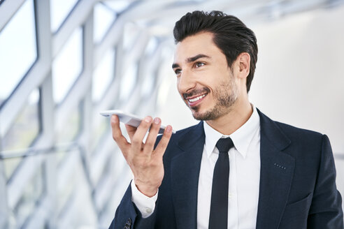 Smiling businessman using smartphone - BSZF00507