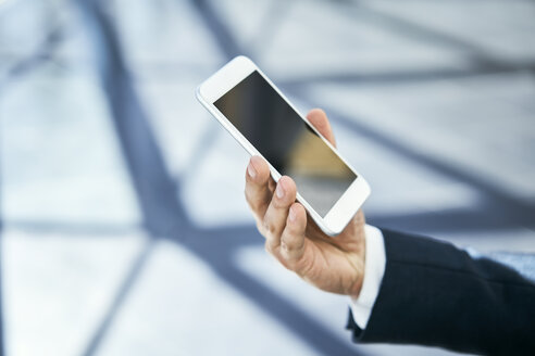 Close-up of businessman holding cell phone - BSZF00510