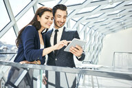 Businesswoman and businessman sharing tablet in modern office - BSZF00519
