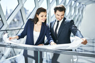 Smiling businesswoman and businessman looking at plan in office - BSZF00522
