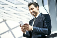 Smiling businessman looking at cell phone - BSZF00534