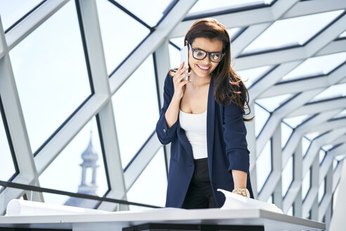 Smiling businesswoman on cell phone looking at plan in office - BSZF00543