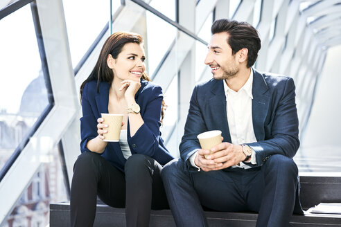 Smiling businesswoman and businessman having a coffee break in modern office - BSZF00549