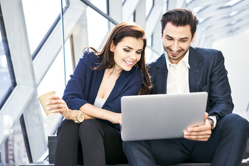 Smiling businesswoman and businessman sharing laptop on stairs in modern office - BSZF00552