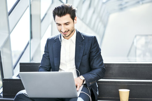 Smiling businessman sitting on stairs wearing earphones and using laptop - BSZF00555