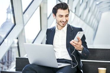 Smiling businessman sitting on stairs wearing earphones using cell phone and laptop - BSZF00558