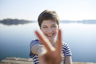 Portrait of smiling woman in front of lake showing victory sign - PNEF00649