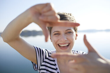 Portrait of laughing woman in front of lake shaping frame with her fingers - PNEF00652