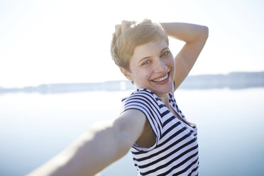 Portrait of happy woman standing in front of lake - PNEF00658