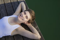Portrait of smiling woman lying on jetty - PNEF00661