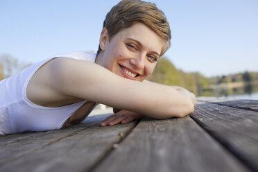 Portrait of happy woman lying on jetty - PNEF00664