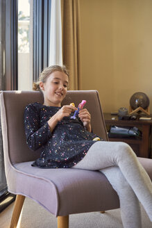 Smiling girl sitting on armchair at home playing with doll - BEF00138