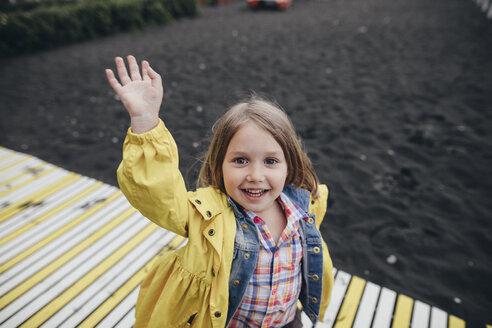 Portrait of smiling little girl on boardwalk on black lava beach - KMKF00251