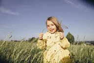 Portrait of smiling little girl on meadow - KMKF00257