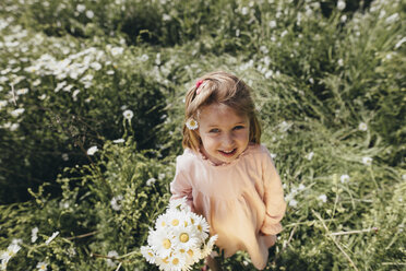 Portrait of little girl with bunch of picked flowers on a meadow - KMKF00269