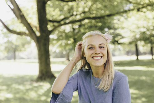 Portrait of happy young woman in a park - KMKF00278