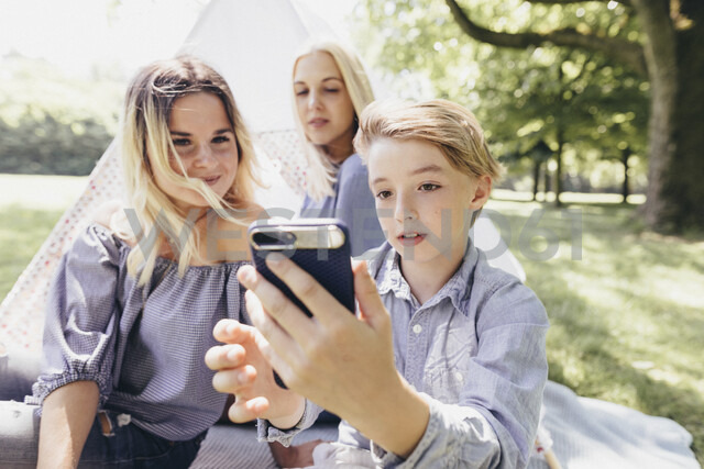 Two young women and a boy taking a selfie next to teepee in a park - KMKF00281