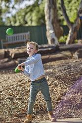 Boy in garden playing with foam baseball bat and ball - BEF00152