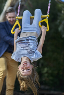 Girl hanging on trapeze with father in background - BEF00158