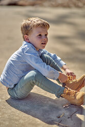 Boy sitting outdoors lacing his boots - BEF00161