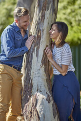 Couple at tree trunk smiling at each other - BEF00164