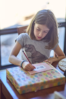 Girl writing gift card at table - BEF00167
