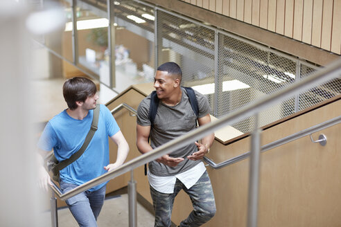 Two male students moving up stairway at higher education college - CUF22182