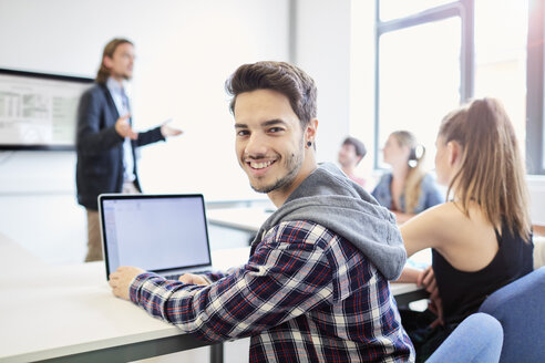 Portrait of young male student using laptop in higher education college classroom - CUF22188