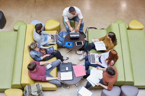 Overhead view of seven male and female students brainstorming in higher education college study space - CUF22200