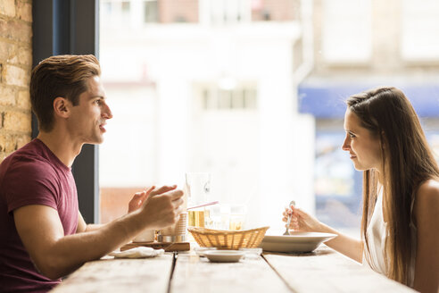 Young couple chatting whilst eating in restaurant - CUF22275