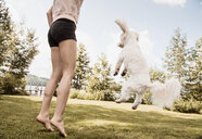 Woman jumping with coton de tulear dog in garden, Orivesi, Finland - CUF22383
