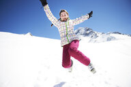 Teenager girl jumping in snow - ISF08113