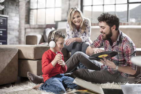 Parents showing vinyl record to son at home - ISF08179