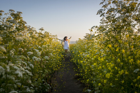 Woman walking through field of wildflowers - ISF08288