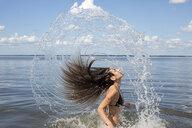Young woman splashing and throwing back long hair from sea, Santa Rosa Beach, Florida, USA - ISF08366