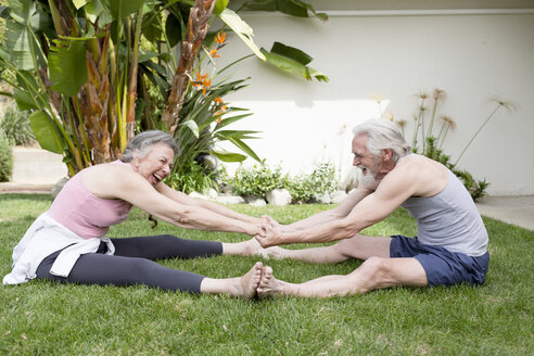 Senior couple sitting on garden lawn holding hands doing resistance exercises - ISF08411