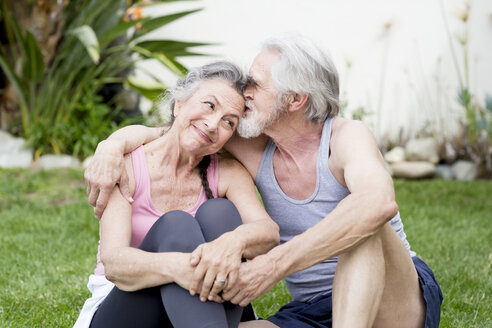 Romantic senior couple sitting on garden lawn taking an exercise break - ISF08414