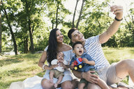 Parents with baby and toddler sons taking smartphone selfie in Pelham Bay Park, Bronx, New York, USA - ISF08516