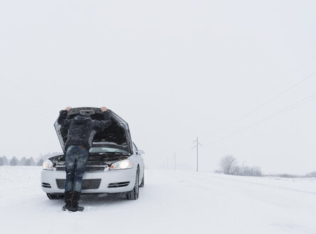 Rear view of man looking under hood of broken down car on snow covered landscape - ISF08555