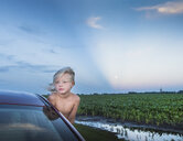 Boy leaning out of car window looking away - ISF08567