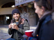Young couple sitting outside holding hot drinks - ISF08669