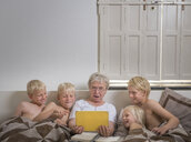 Grandmother in bed with grandsons using digital tablet - CUF22745