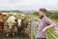 Man leaning against gate on cow farm looking away - CUF22793