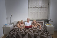 Grandmother in bed with grandsons reading story book - CUF22796