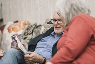 Senior couple reading book on couch - CUF22811